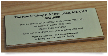 brass plaque mirror polished with black paint fill mounted on a timber base