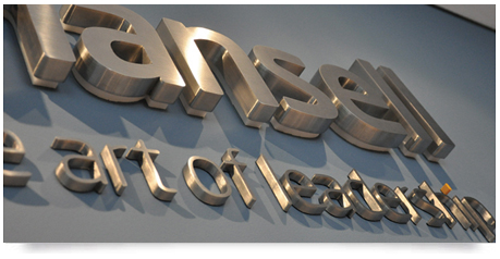 thick fabricated stainless steel letters mounted to a office wall with a drop shadow effect